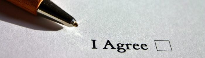 "A photo of a pen on paper, which reads, ""I Agree"" next to an empty checkbox."