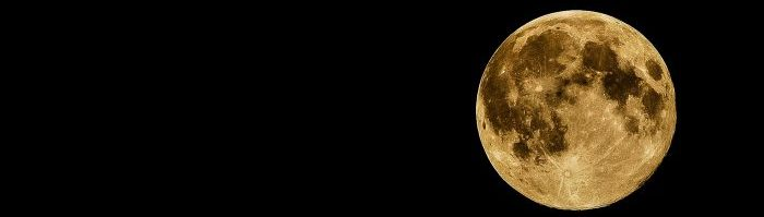 A photo of a yellow moon against a black background.
