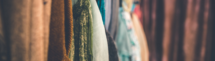 A photo of a rack of clothing up close. There are lots of different textures.
