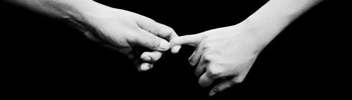 A photo of one hand holding another by the pinky.