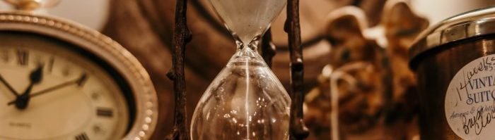 A photo of a clock, hourglass, and other antique objects.
