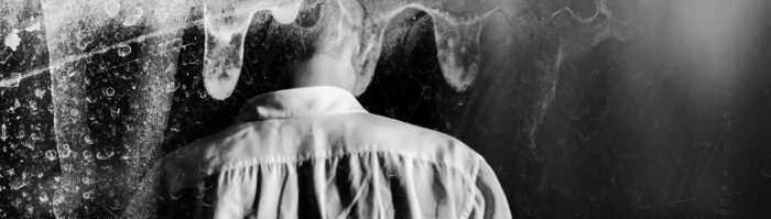 A photo of a person from behind surrounded by smoke.