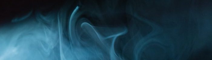 A photo of blue smoke against a dark background.
