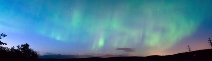 A photo of the Northern Lights above a dark skyline.