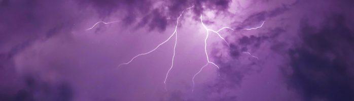 A photo of a lightning bolt against a purple sky.